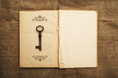 24435697 - vintage open book with old grunge paper textured pages and rusty key