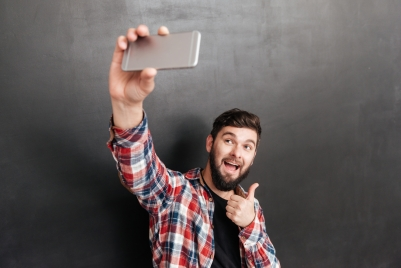Cheerful bearded young man showing thumbs up and taking selfie