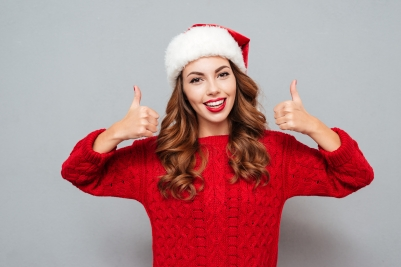 Cheerful young woman in santa claus hat showing thumbs up