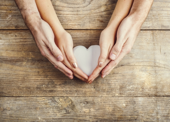 Hands of man and woman holding a heart together. Studio shot on a wooden background, view from above.