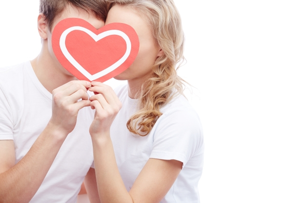 Portrait of amorous young couple holding red heart by their faces