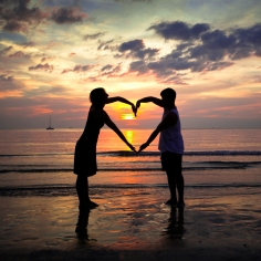 Young couple holding hands heart-shaped on the sea beach at sunset